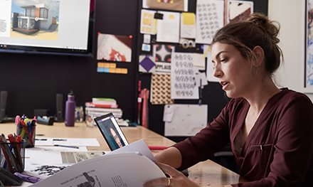Image for: An image of a female small business professional working on designs using devices running PowerPoint and Microsoft Teams.