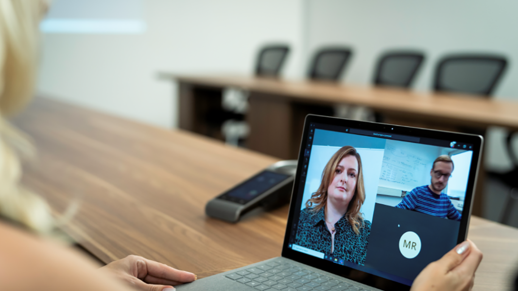 An image of a blond haired woman in an empty conference room using a Surface laptop to make a Microsoft Teams video call with three other people.