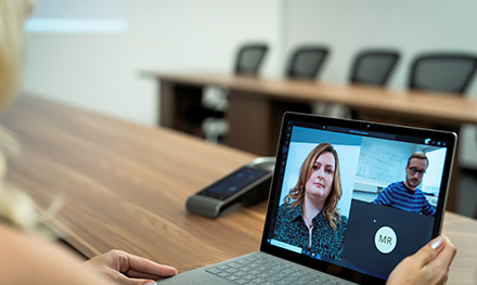 Image for: An image of a blond haired woman in an empty conference room using a Surface laptop to make a Microsoft Teams video call with three other people.