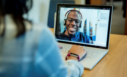 Image for: Image of a woman at a desk using a Surface laptop to make a Microsoft Teams video call with one man smiling and wearing a headset.
