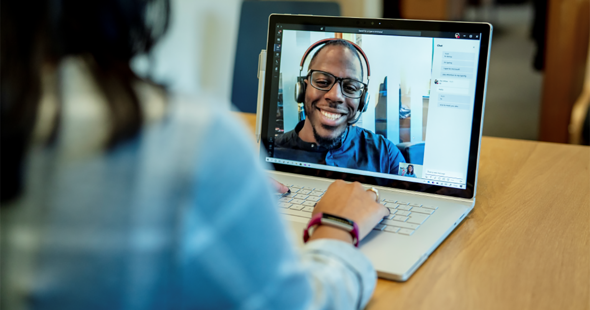 Image of a woman at a desk using a Surface laptop to make a Microsoft Teams video call with one man smiling and wearing a headset.