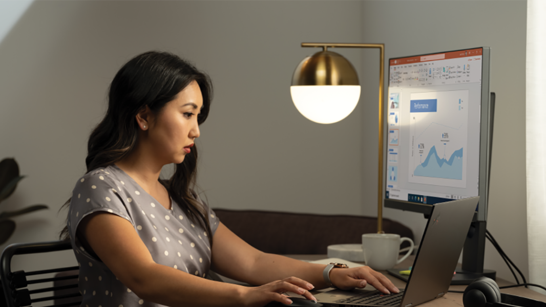 An image of a woman working at her home office on a Lenovo ThinkPad Yoga connected to an external monitor.
