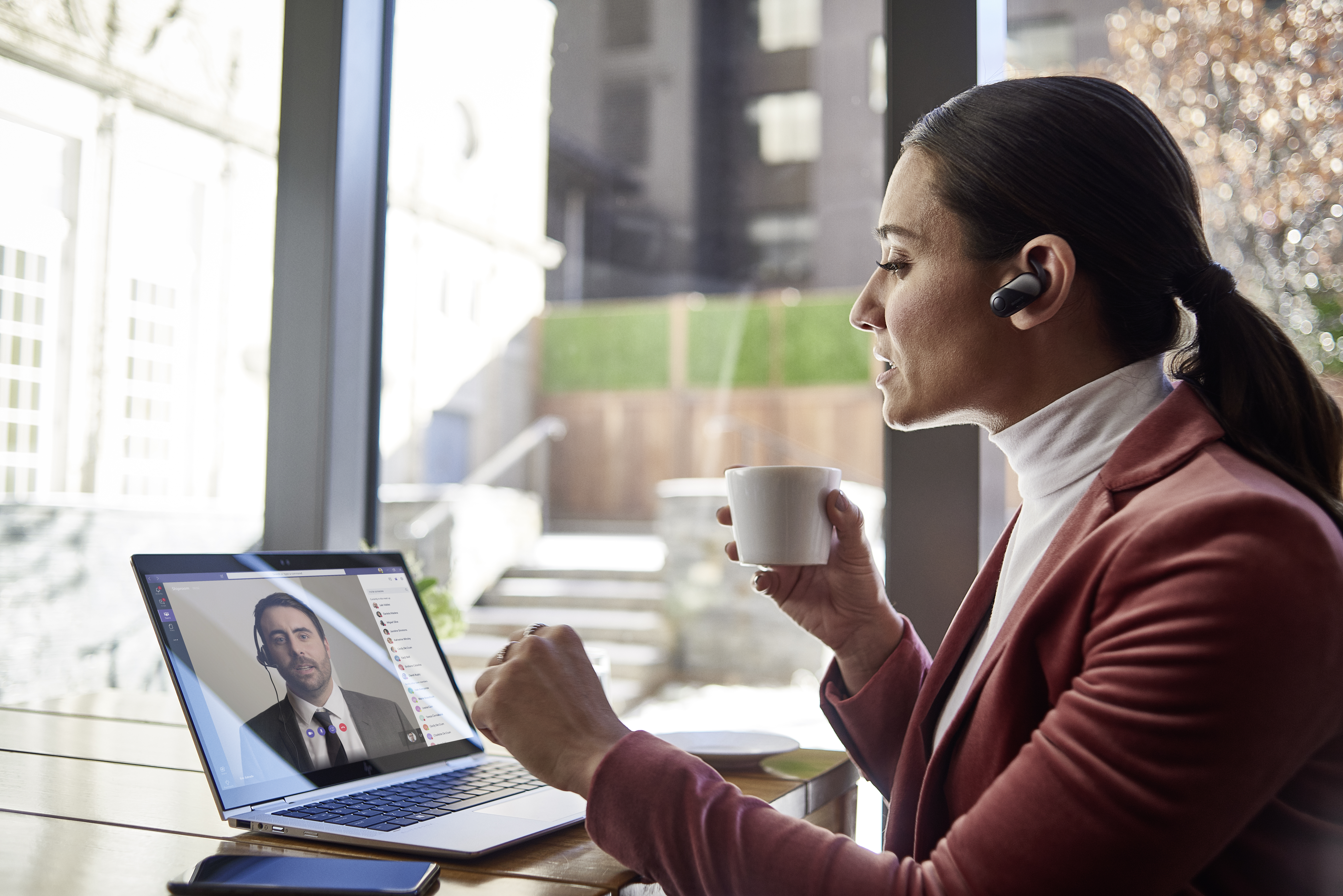 Image for: Female small business executive using HP Elite device running Microsoft Teams conference call. Different screens are available: one featuring 1 person on screen, another with 9 people on screen. Keywords: Microsoft Teams, Bluetooth, coffee.