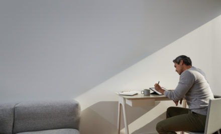 Image for: Adult male in home office environment sitting at a desk with a black Microsoft Surface Pro 7 in studio mode. Black Microsoft Surface Pen in hand.