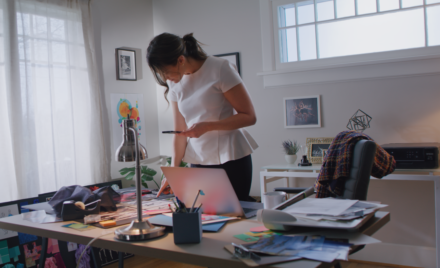 Image for: image of a woman standing over a desk at home, looking down at her laptop