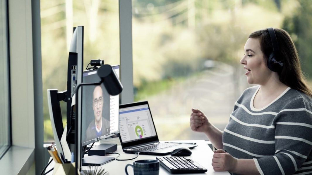 Female enterprise employee working remotely from her home office, chatting with a headset on.