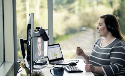 Image for: Female enterprise employee working remotely from her home office, chatting with a headset on.