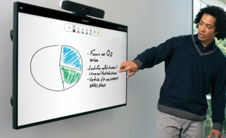 Image for: One male pointing to a wall-mounted display featuring whiteboard functinality with a Poly Microsoft Teams Rooms on Android collaboration bar wall on top of the display