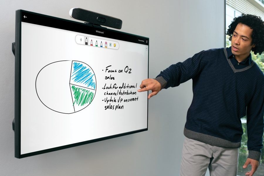 One male pointing to a wall-mounted display featuring whiteboard functinality with a Poly Microsoft Teams Rooms on Android collaboration bar wall on top of the display