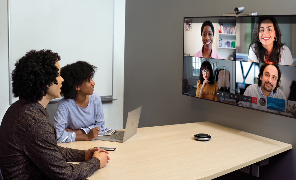 Two coworkers in conference room on a Microsoft Teams call with four other people