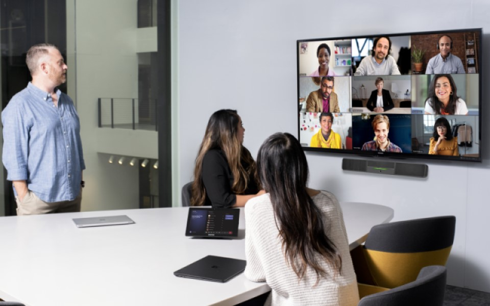 Image of a team on a Microsoft Teams meeting featured on a big screen