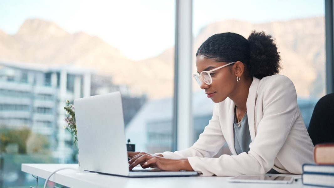 Picture of a woman wearing a white blazer and glasses, looking down at a laptop on her desk.