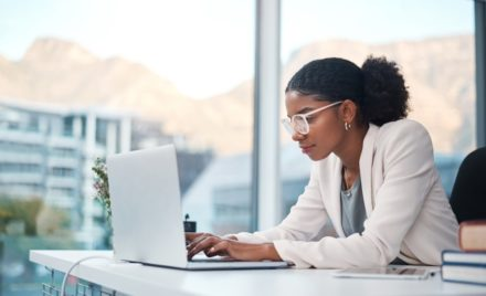 Image for: Picture of a woman wearing a white blazer and glasses, looking down at a laptop on her desk.