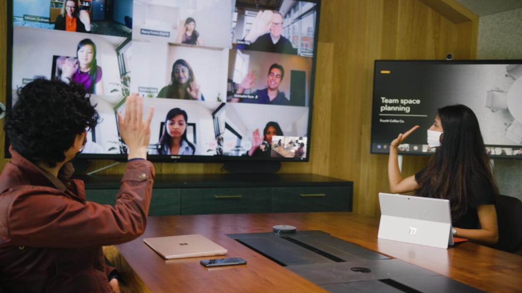 Изображение, показывающее людей, сотрудничающих в цифровом формате и лично в переговорной комнате от Microsoft Teams