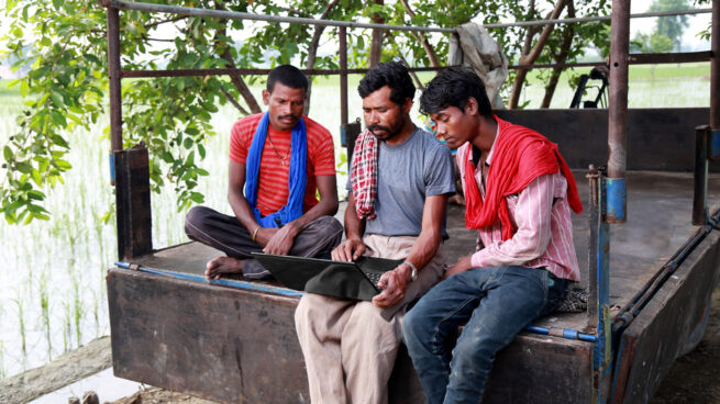 Three men sitting on the back of a truck watching a mobile device