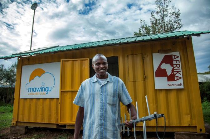Benson Maina holds a TV white spaces antenna in front of the Mawingu White Spaces Broadband pilot container near Nanyuki, Kenya. The pilot offers the public access to Wi-Fi, devices and services free of charge. (Photo credit: Georgina Goodwin)