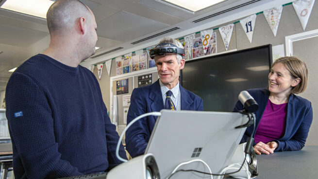 Peter Bosher, middle, an audio engineer who is blind who worked with the Project Tokyo team early in the design process, checks out the latest iteration of the system at Microsoft's research lab in Cambridge, UK, with researchers Martin Grayson, left, and Cecily Morrison, right. Photo by Jonathan Banks.