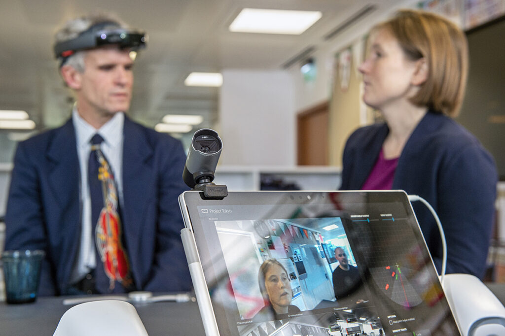 Peter Bosher, left background, an audio engineer who is blind, checks out the latest iteration of the Project Tokyo system at Microsoft's research lab in Cambridge, UK. Bosher wears a modified Microsoft HoloLens that streams images of its visual field to computer hardware for processing. A dashboard on the laptop screen shows the visual field. Microsoft researchers Cecily Morrison, right background, and left on the screen, and Martin Grayson, right on the screen, are visible to the HoloLens. Photo by Jonathan Banks
