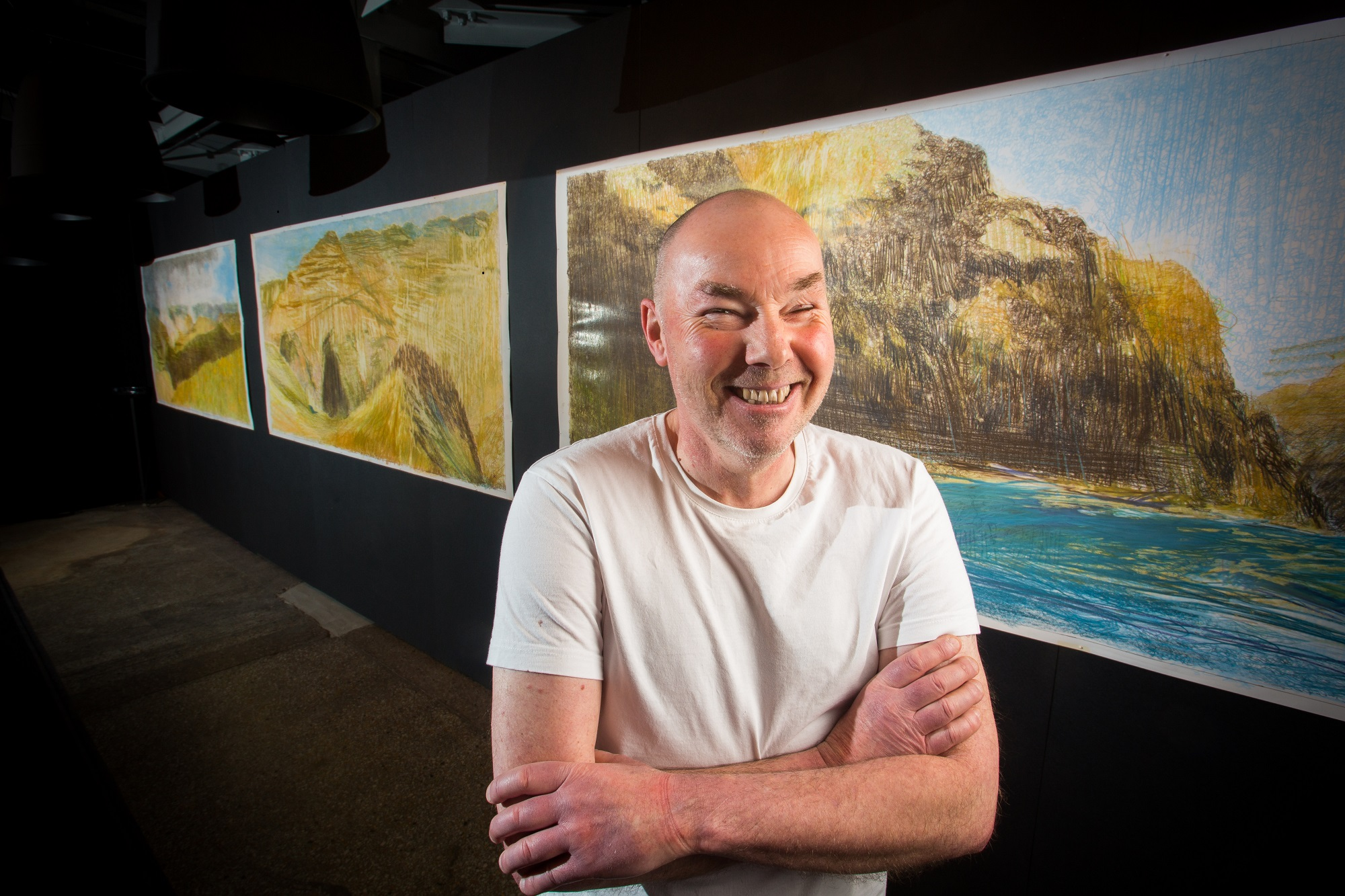 Artist Keith Salmon in front of his paintings of Hells Canyon in