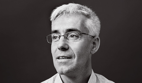 a man wearing glasses and looking at the camera