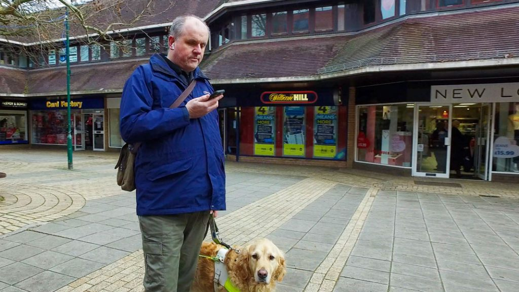 Man holding a smart phone, standing next to his guide dog