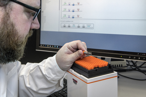 Researcher in Microsoft wet lab examining biological compound