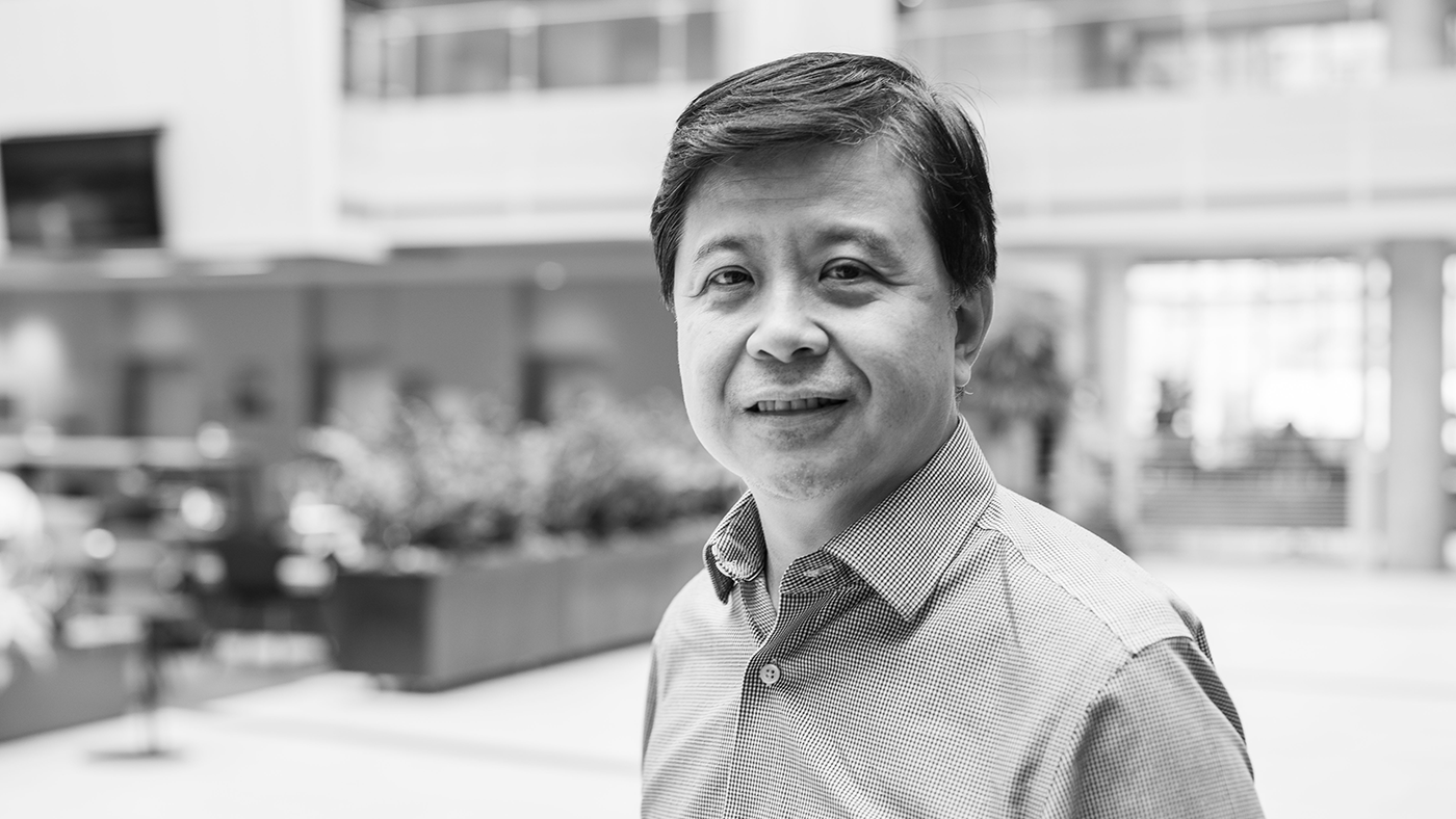 Hsiao-Wuen Hon wearing a suit and tie smiling at the camera