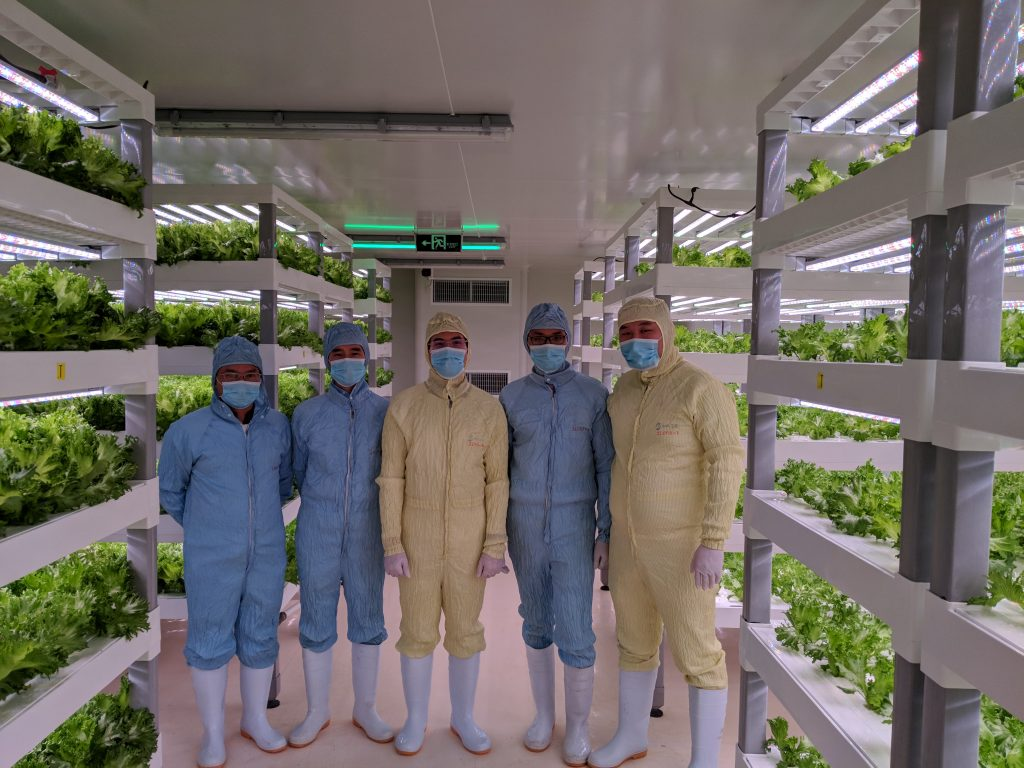 Tran (center) with collaborators from Sananbio at a vertical farm inside the company's Xiamen, China, facility.