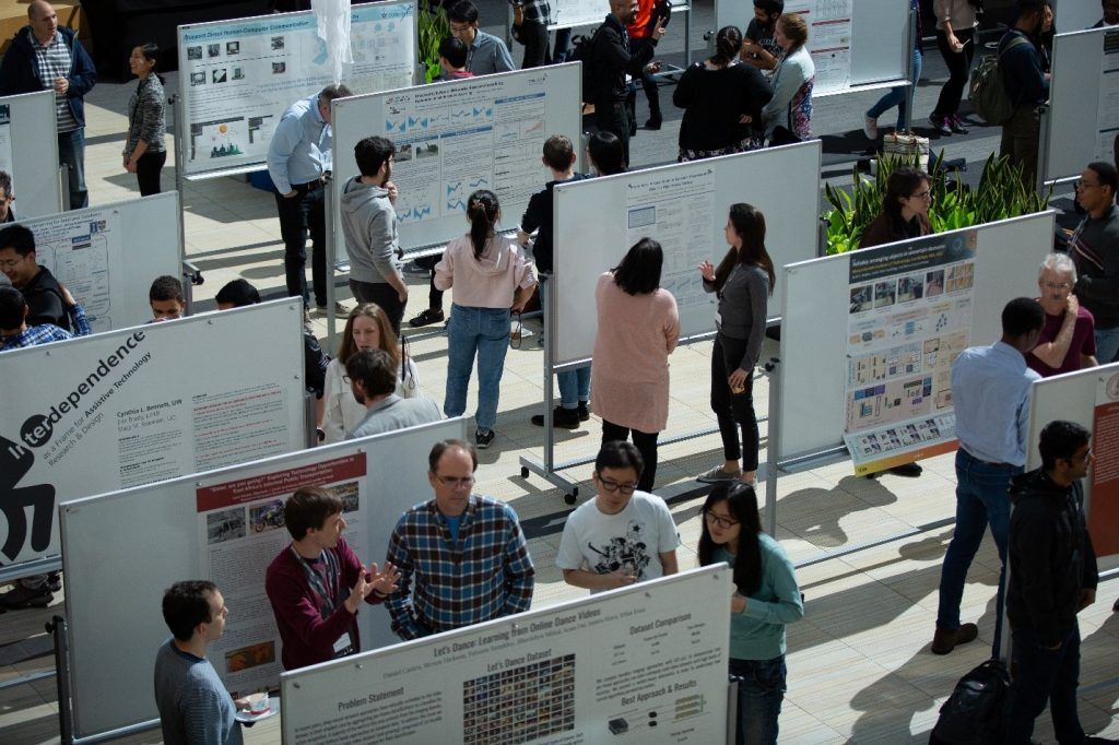 2018 PhD Summit Poster Session ,image of people viewing and engaing with the posters