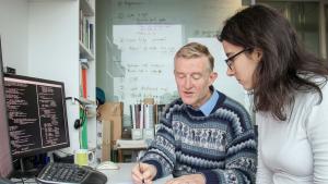 Simon Peyton Jones writing with a fellow researcher at a desk