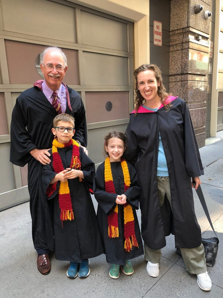 a grandfather, mother, and two children—and they are dressed in Harry Potter costumes.