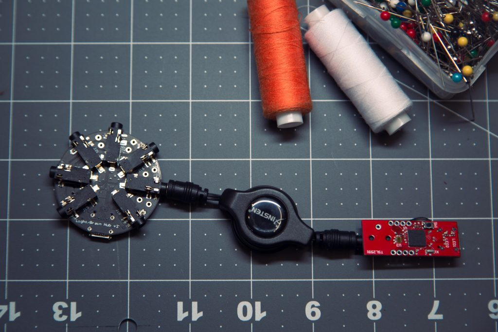 "For the fashion application, the plug-and-play microcontroller technology included two core hardware components, both custom-made with SAMD21 microcontrollers: the ""brain"" and the ""beads."" Each of the color-coded beads, or sensors, responded to a different stimulus. The red bead (above, right) is a light sensor bead."