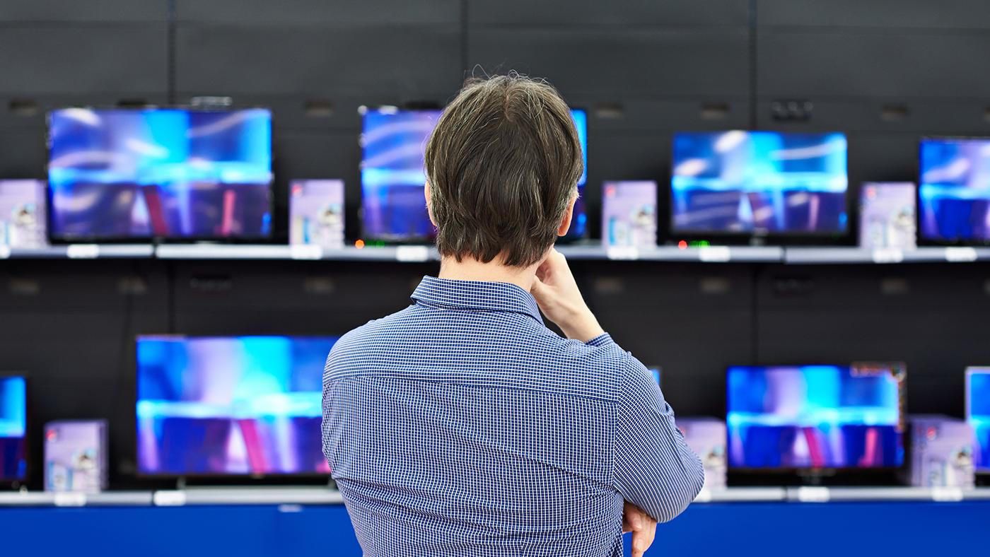 Person looking at televisions for sale in a department store.