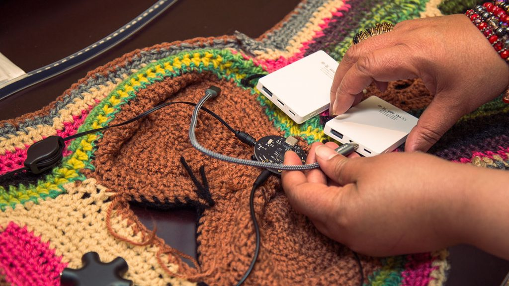 Project Brookdale: photo of a woman's hands plugging in the circuits woven into garment