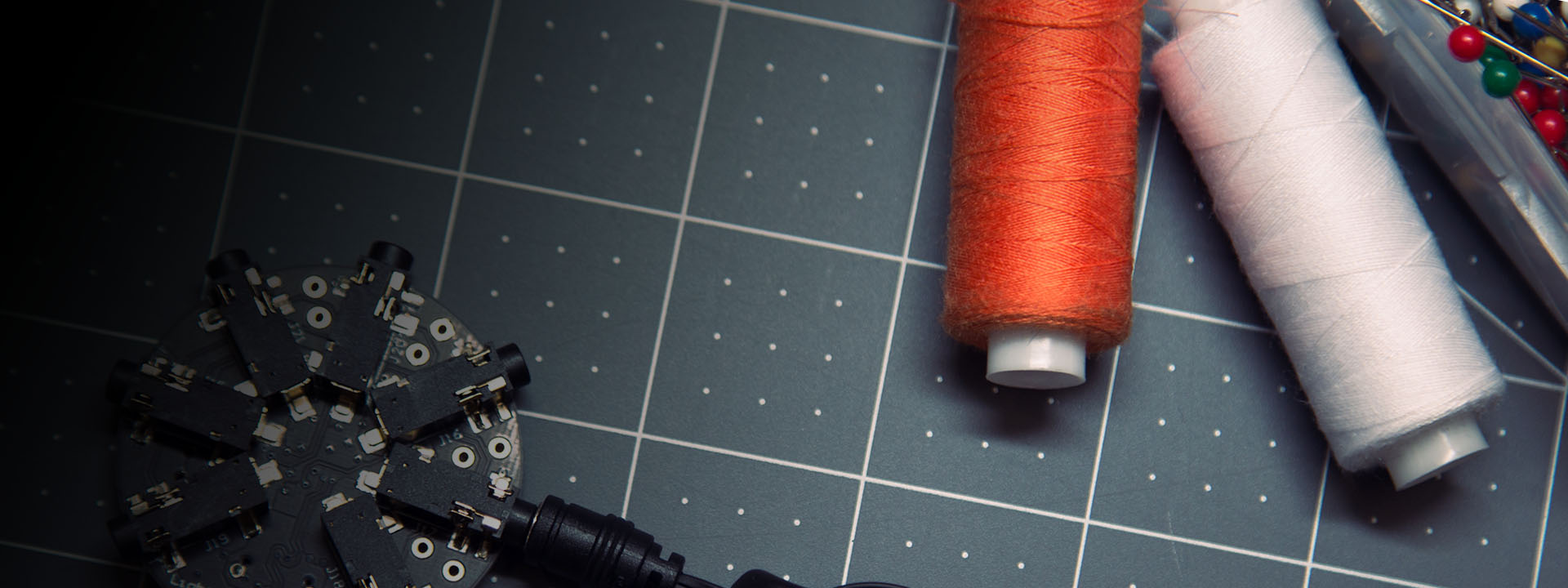 Project Brookdale: photo of a round circuit, spools of orange and white thread, and a box of colorful beads