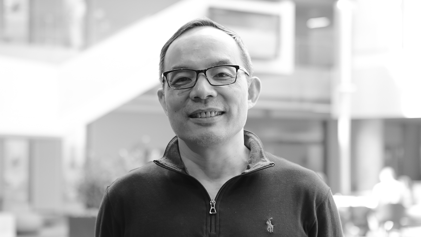 Xuedong Huang wearing glasses and smiling at the camera