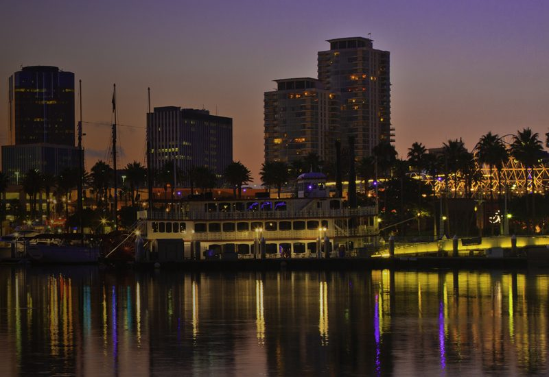 Rainbow Harbor at Long Beach Marina, California with city skyline at sunset