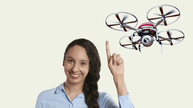 Woman smiling and pointing at a drone flying in the air