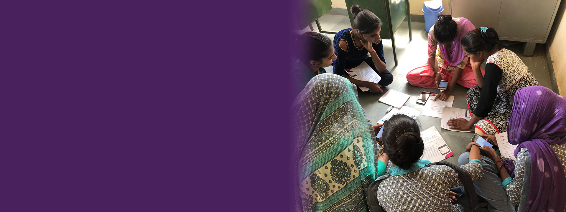 SCAI header - photo a a group of women sitting on the floor working on their phones