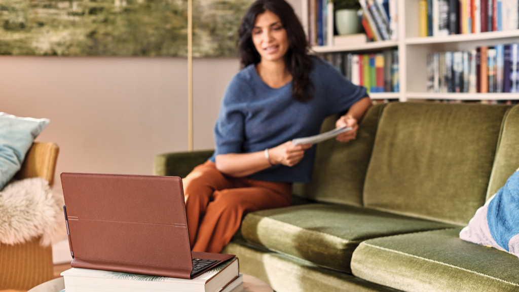 women sits on green couch looking at a tablet on the coffee table in front of her