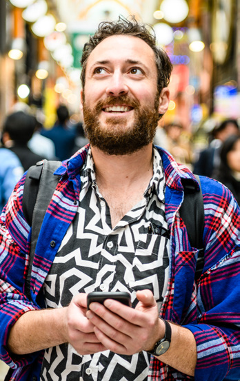 Male tourist in patterned shirt holding a cellphone looking up on busy street