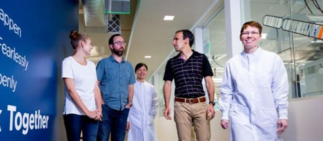 Group of men and women walking down a lab hallway