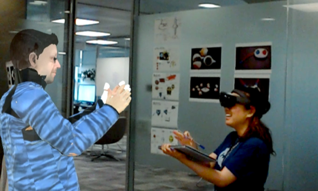 Senior Researcher Sean Rintel, using VROOM, interacts with Research Assistant Priscilla Wong, who is wearing a HoloLens. Sean's photorealistic avatar is clapping along with Priscilla.