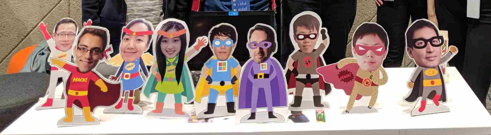 Small cardboard cutouts of VROOM hackathon team members propped up on a table. Each cutout has a photograph of the team member's face paired with a cartoon superhero body.