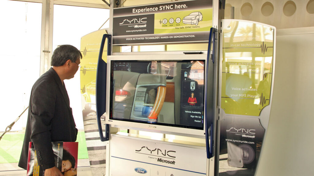 audio and acoustics: man standing in front of Experience Ford SYNC kiosk