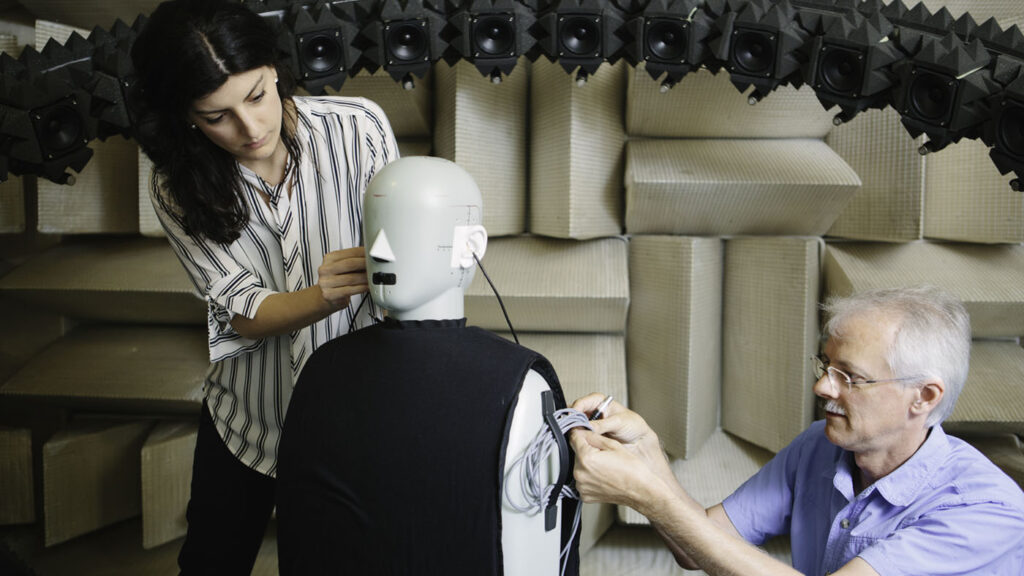 audio and acoustics: woman and man setting up a dummy in anachoic chamber