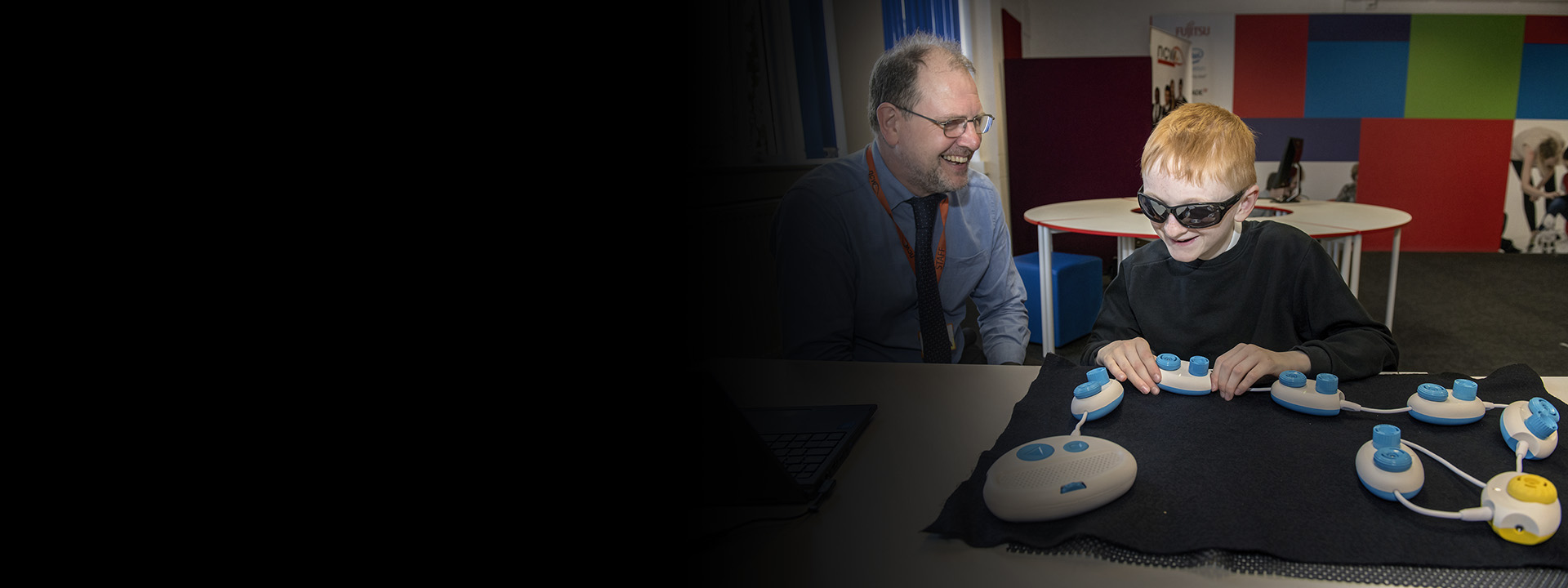 Young blind person learning to code tactilely using Code Jumper pods as teacher looks on. Photo by Jonathan Banks.