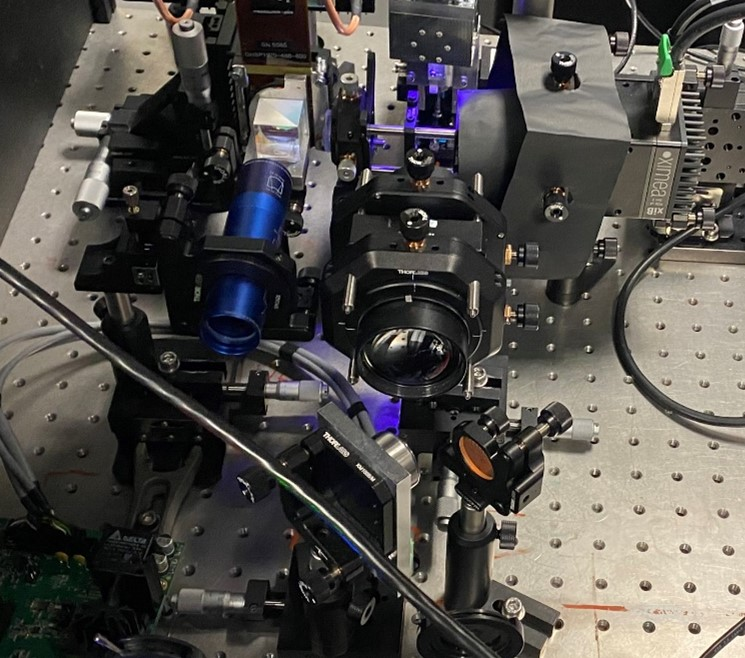 A workbench that shows a holographic storage experimental testbed, which includes an array of lenses, mirrors, and other components.