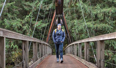 Lucas Joppa walking across a wooden bridge