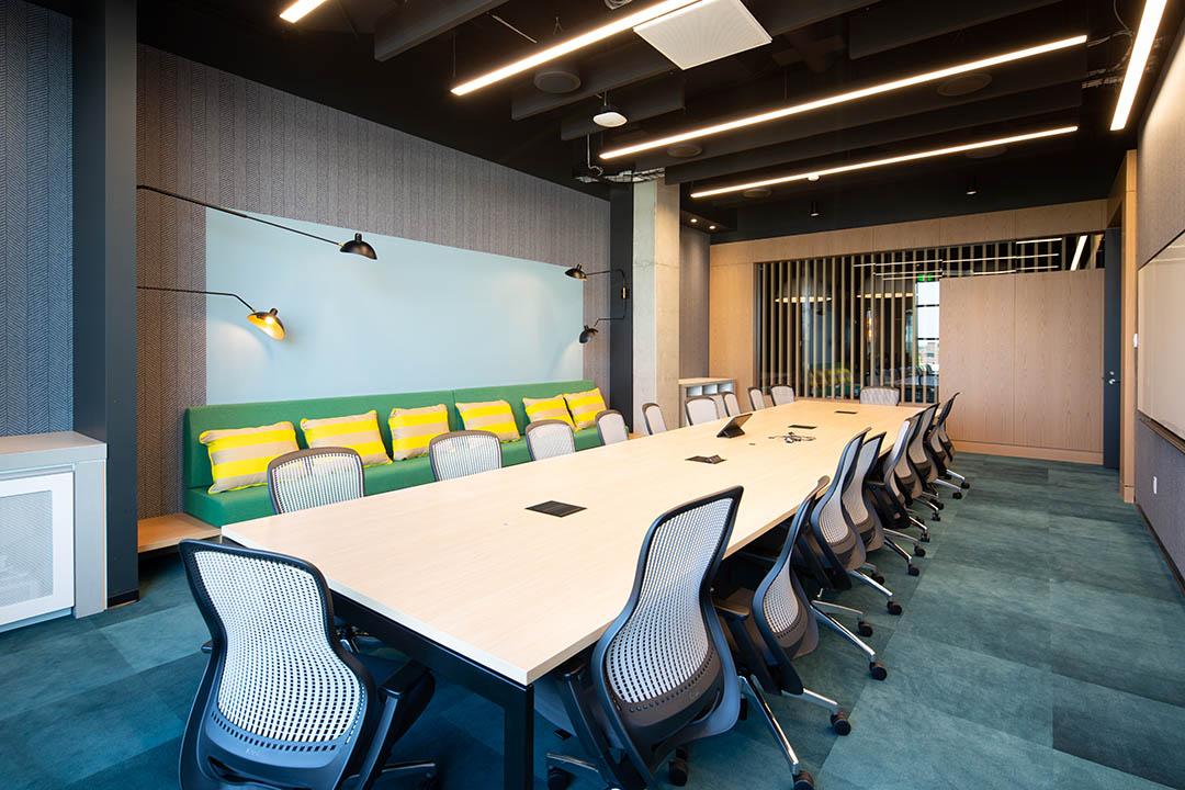 A large office space with a long table and chairs, bench seating, and whiteboard at Microsoft Research Montreal. Un grand espace de bureau avec une longue table et des chaises, des sièges de banc et un tableau blanc chez Microsoft Research Montréal.